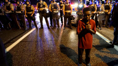 Amarion Allen, 11-years-old, stands in front of a police line during protests in Ferguson, Missouri, in 2015.