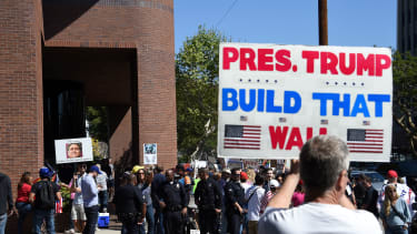 A demonstrator holds a sign supporting a border wall.