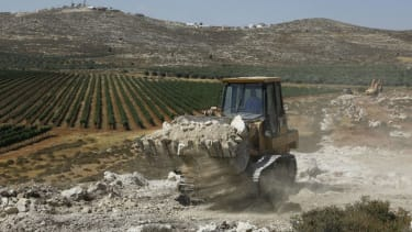 A bulldozer clears land in the West Bank.