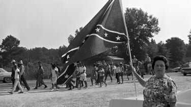 A white woman stands in protest with a Confederate flag
