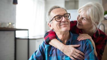 Older couple hug.