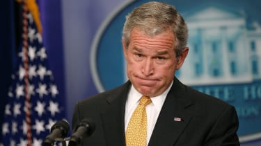 George W. Bush looks frustrated, pursing his lips and puffing his cheeks.