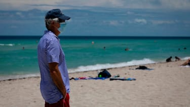 A man wears a mask on the beach in Miami.