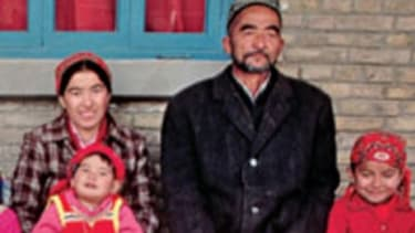A Muslim Uighur man rests with his two wives and their six children in front of their house at the Buzak Commune. Near Khotan, Xinjiang Province, People's Republic of China.