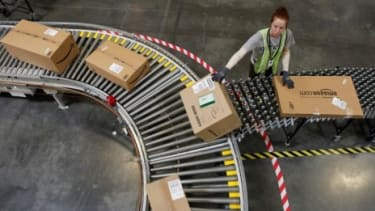 An Amazon employee sorts packages in Arizona: The online retailing giant's deep discounts may be its demise.