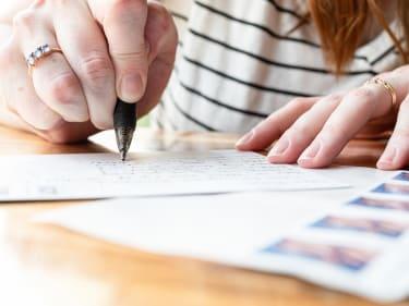 A woman writes a postcard.