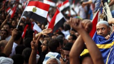 Supporters of Muslim Brotherhood's presidential candidate Mohamed Morsi celebrate his victory Sunday: As promised, Morsi resigned from the Brotherhood, saying he serves all of Egypt.
