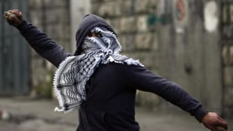A young Palestinian man prepares to throw a stone.