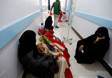 Women wait in a hospital hallway with children suspected to be infected with cholera.