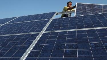 Worker installing solar panels.