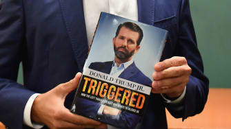 Donald Trump Jr. holds a copy of his new book.