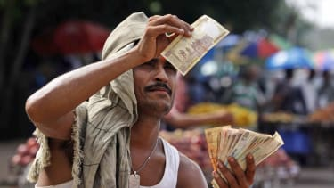 A street vender checks the authenticity of a rupee.