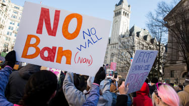 Protesters stand up against the immigration executive order by President Trump.