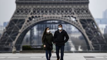 People wear masks in front of the Eiffel Tower.