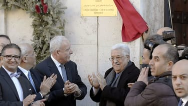 Palestinian president Mahmud Abbas (C, R) applauds after he inaugurated the new Palestinian diplomatic mission to the Holy See
