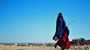 A woman walks through drought conditions in Somalia