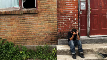 A child sits on a stoop in a working class section of Utica, New York.