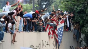 Egyptians replace the American flag with a black Islamic flag at the U.S. embassy in Cairo