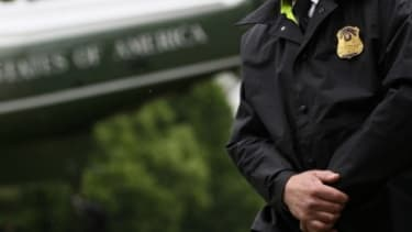 A uniformed Secret Service agent stands his post as President Obama departs the White House.
