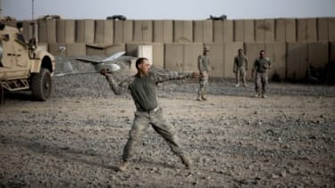 A U.S. soldier prepares to deploy a Raven unmanned surveillance drone in Afghanistan in 2010: The military is shifting its strategy to the cheaper, more reliant robotic airplanes.