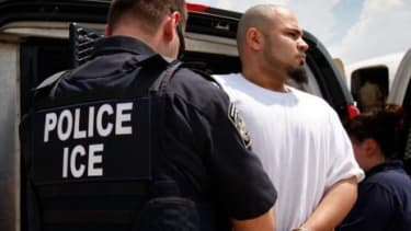 An undocumented immigrant is moved from a van to a jet chartered by U.S. Immigration and Customs Enforcement (ICE).