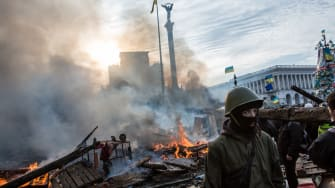 Anti-government protesters walk amid debris and flames near the perimeter of Independence Square, known as Maidan, on February 19, 2014 in Kiev, Ukraine.