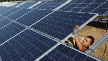 A worker installs solar panels containing photovoltaic cells at the new Solarpark Eggersdorf solar park near Muencheberg, Germany.
