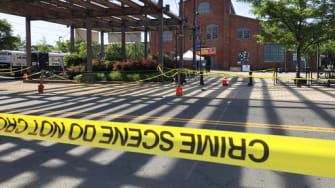 Police crime-scene tape keeps people away from the brick Roebling Wire Works building, background, in Trenton, N.J., hours after a shooting broke out there at an all-night art festival early