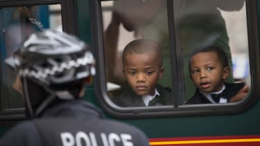 Boys watch from a seat in a charter bus as demonstrators march in protest of police abuse in Chicago.
