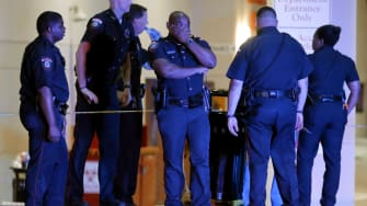A police officer covers his face while standing outside the emergency room after the Dallas attacks.