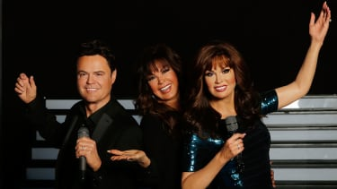 Marie Osmond with wax figures of her brother Donny and herself.