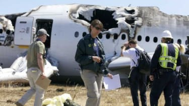An NTSB investigator examines scattered debris on the scene of the Asiana Airlines crash.