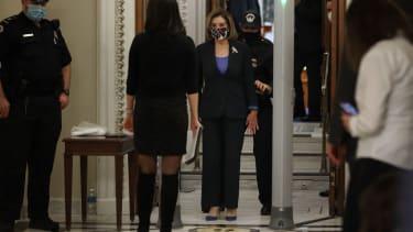 Nancy Pelosi walks through a metal detector
