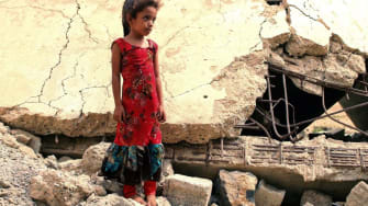 A displaced Yemeni girl stands in rubble.