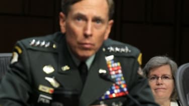 Gen. David Petraeus listens as his wife (right) looks on during a confirmation hearing in 2011: The CIA Director abruptly resigned on Friday, citing an extramarital affair.