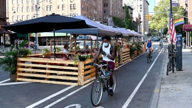 A person on a bicycle wearing a face mask rides past outdoor seating as the city continues Phase 4 of re-opening following restrictions imposed to slow the spread of coronavirus on August 11,