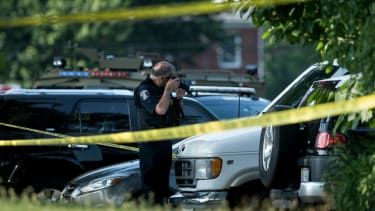 Officer photographing scene of shooting.