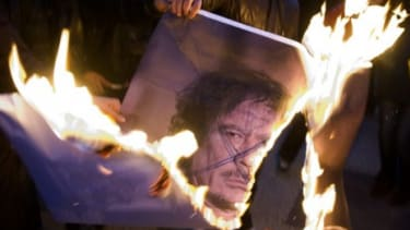 Protesters burn a photo of Moammar Gadhafi: Already, Libya's new leaders are debating how to deal with the toppled despot once he is caught.