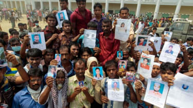 A Bangladeshi display pictures of missing relatives outside the site of the building collapse.