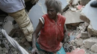 A woman emerges from the rubble caused by the catastrophic earthquake that struck Haiti on January 12, 2010.