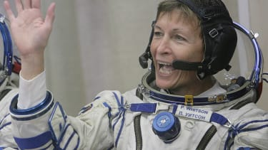 Peggy Whitson waves in her spacesuit.