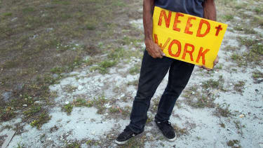 An unemployed man works a street corner hoping for a job.