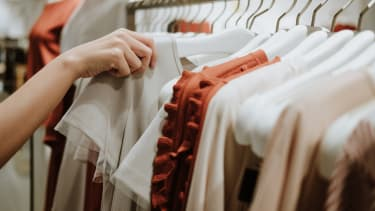 A woman reaches for clothes on a rack.
