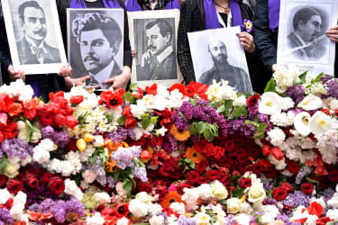 People hold photos of victims of the Armenian Genocide.