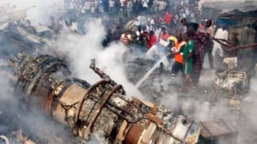 Firefighters try to put out the fire at the site of a plane crash near the Lagos airport in Nigeria on June 3. The passenger plane carrying 153 people crashed into a building on Sunday, killi