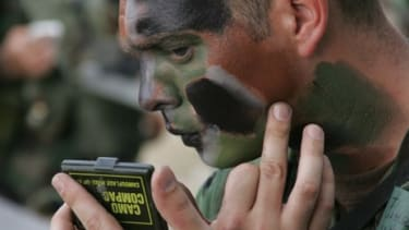 A U.S. Air Force airman applies camouflage makeup before an urban training session in 2006