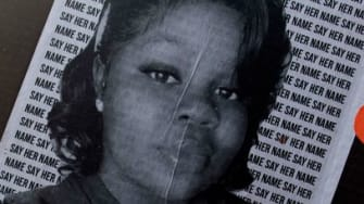 A protester holds a sign with Breonna Taylor's picture.