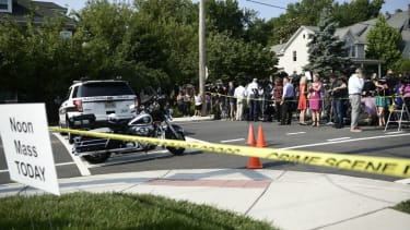 Crowds held back by police tape at scene of shooting.