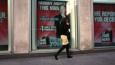 A woman walks by an ad for Bill O'Reilly's television show.