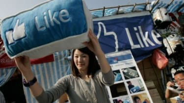 A woman displays a Facebook cushion on sale in China